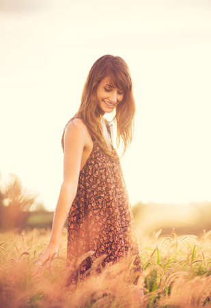 Beautiful young woman outdoors. Romantic Model in Sun Dress in Golden Field at Sunset. Happy Emotions, Glowing Sunlight. Backlit. Warm color tones  Stock Photo