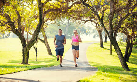 Athletic couple running together. Sport runners jogging on park trail in the early morning.  Healthy lifestyle fitness concept