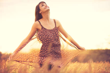 Beautiful young woman outdoors. Romantic Model in Sun Dress in Golden Field at Sunset. Enjoying Glowing Sunlight. Backlit. Warm color tones with slight Motion Blur photo