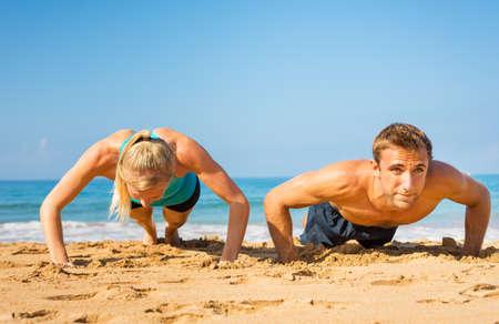 push: Athletic couple doing push ups on the beach, workout training Stock Photo
