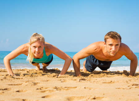 push up: Athletic couple doing push ups on the beach, workout training Stock Photo