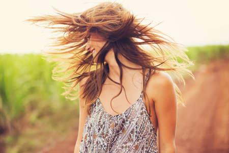 Nádherná romantická dívka venku. Krásný model v krátké šaty v poli. Dlouhé vlasy vlající ve větru. Podsvícený, teplé barevné tóny