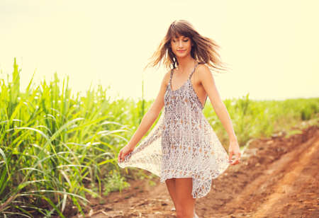 Gorgeous Romantic Girl Outdoors. Beautiful  Model in Short Dress in Field. Long Hair Blowing in the Wind. Backlit, Warm Color Tones photo