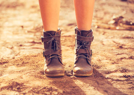 mud woman: Close up view of woman wearing stylish boots on dusty road Stock Photo