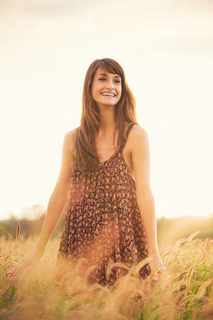 Beautiful happy woman in golden field at sunset, Carefree healthy lifestyle, Vibrant color, Backlit warm tones photo
