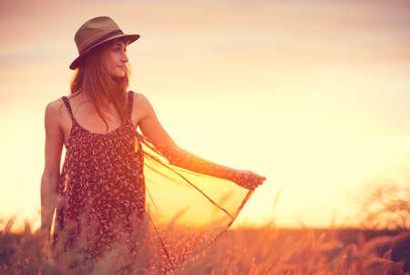 Krásná žena v zlatém poli při západu slunce, Fashion životní styl, zářivé barvy, podsvícený teplé tóny Reklamní fotografie