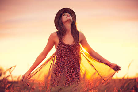 Beautiful woman in golden field at sunset, Fashion lifestyle, Vibrant color, Backlit warm tones photo