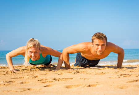 Athletic couple doing push ups on the beach, workout training 스톡 콘텐츠