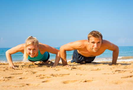 Athletic couple doing push ups on the beach, workout training Stock Photo