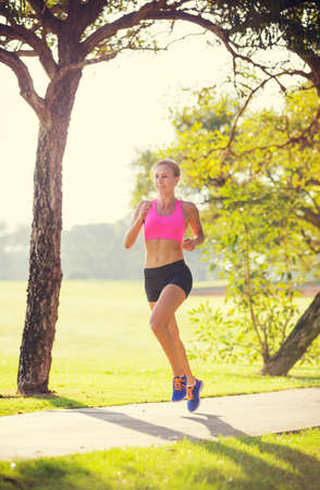 Athletic woman running in park in the early morning