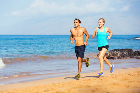 athlete running: Athletic sporty couple jogging together on the beach