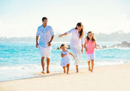 Gelukkige familie plezier op het strand loopt Stockfoto
