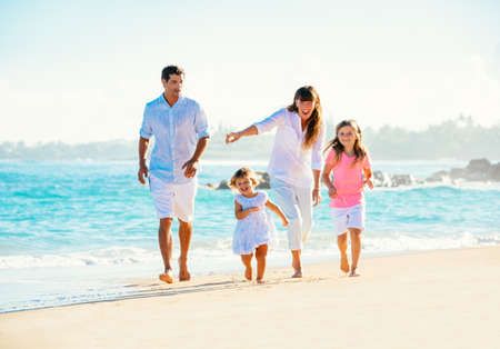 Happy family having fun walking on the beach