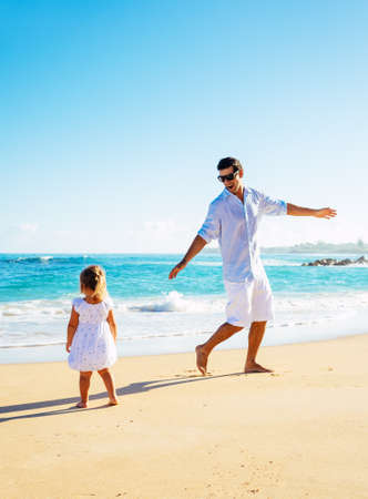 Healthy father and daughter playing together at the beach  Stock Photo