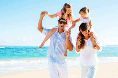 Happy family having fun on the beach Imagens
