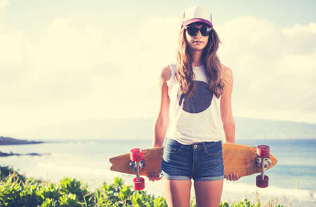 red head girl: Beautiful hipster girl with skate board wearing sunglasses