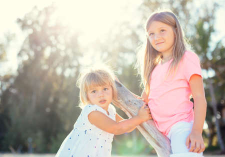 Adorable young sisters, cute little girls together at the beach