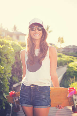 Beautiful hipster girl with skate board wearing sunglasses