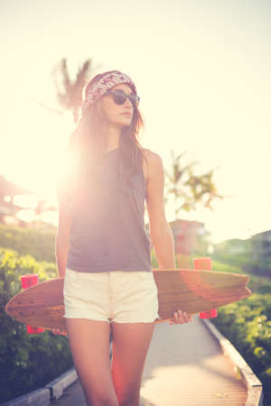 Beautiful hipster girl with skate board wearing sunglasses photo