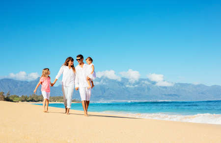 latin family: Happy family walking on the beach