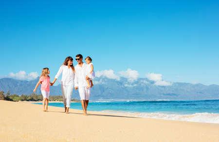 latin girl: Happy family walking on the beach