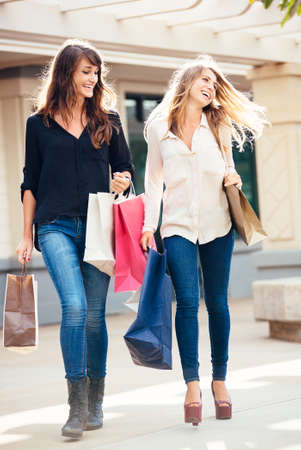 Two happy young women shopping at the mall photo
