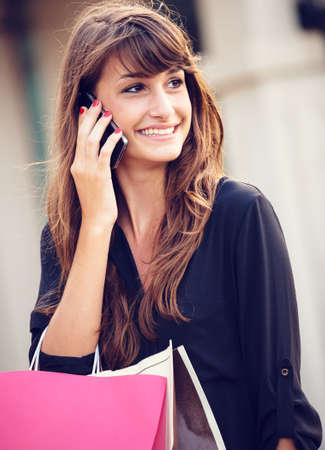 Attractive young woman shopping at the mall using cell phone photo