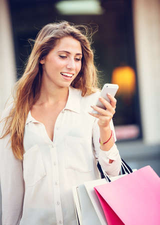 Attractive young woman shopping at the mall using cell phone Stock Photo - 26326823