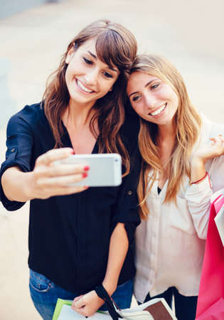 Two young women shopping at the mall taking a selfie or self portrait with their cell phone