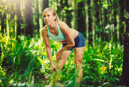 Athletic Woman Stretching Before going for Run in the Forest