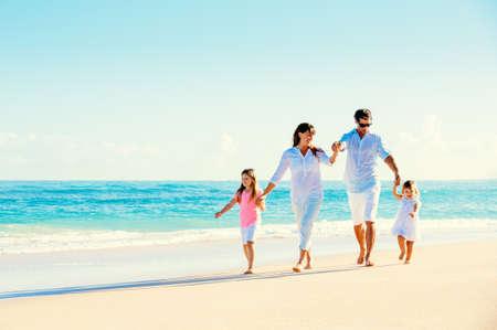 美しい晴れたビーチで楽しんで幸せな家族