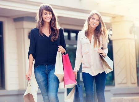 歩いてショッピング モールに買い物袋を持つ美しい女の子 写真素材