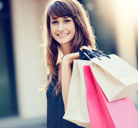 Happy woman holding shopping bags and smiling at the mall Stock Photo