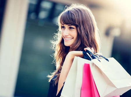 Gelukkige vrouw bedrijf boodschappentassen en lachend in het winkelcentrum