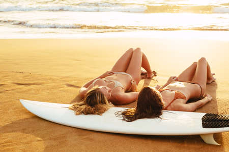 Beautiful surfer girls on the beach at sunset Relaxing on the sand photo