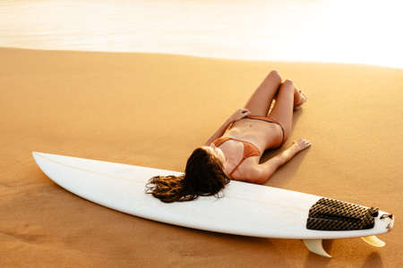 Beautiful surfer girl on the beach at sunset Relaxing on the sand photo