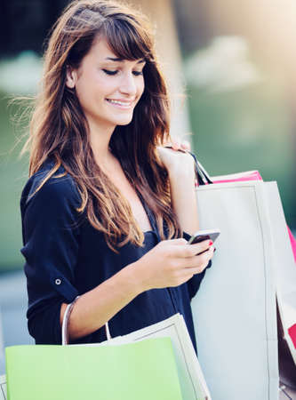 Happy woman holding shopping bags smiling and holding cell phone photo