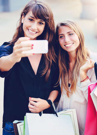 Beautiful girls with shopping bags taking a 'selfie' with their cell phone photo