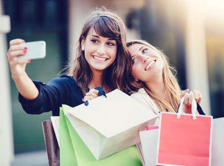 """chicas compras: Hermosas chicas con bolsas de la compra que toman un """"selfie"""" con su teléfono celular"""