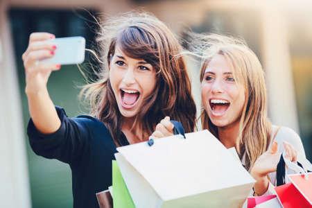 """Mooie meisjes met boodschappentassen nemen van een """"selfie"""" met hun mobiele telefoon Stockfoto - 26962191"""