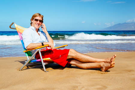 Young Attractive Casual Businessman Entrepreneur Relaxing at the Beach Talking on Cell Phone photo