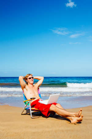 Young Attractive Casual Businessman Entrepreneur Relaxing at the Beach with Laptop Computer  photo