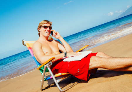 Young Attractive Casual Businessman Entrepreneur Relaxing at the Beach with Laptop Computer Talking on Cell Phone photo