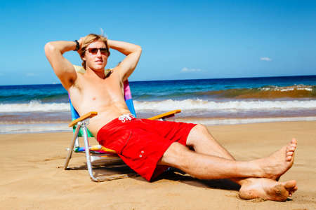 Attractive Handsome Young Man Enjoying Sunny Day on the Beach photo