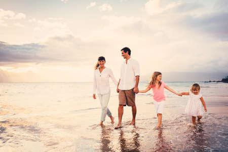 семья: Счастливый молодой семьи веселиться, ходить на пляж на закате