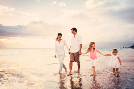 Happy Young Family have Fun Walking on Beach at Sunset Stock Photo