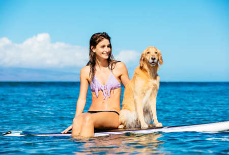 Attractive Young Woman Surfing with her Dog. Sharing surfboard with Golden Retriever. photo