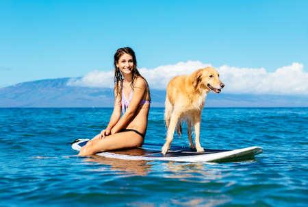 彼女の犬との魅力的な若い女性サーフィン。ゴールデン ・ リトリーバーとサーフボードを共有します。 写真素材