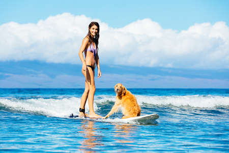 Attractive Young Woman Surfing with her Dog. Riding Wave Together in Ocean. Surfing Dog. photo