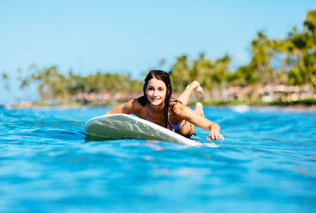 Attractive Young Woman Surfing in Hawaii, Paddling out to the Lineup photo